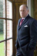 Mature businessman by window, portrait