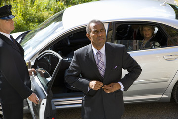 Businessman doing up button of suit jacket, chauffeur holding door of car open