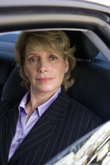 Mature businesswoman in back of car, smiling, portrait