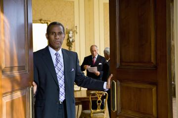 Businessman shutting doors of office, portrait