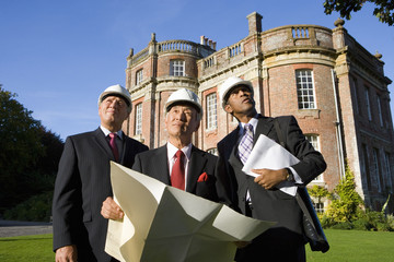 Businessman with blueprint by colleagues, in hardhats, by manor house, low angle view