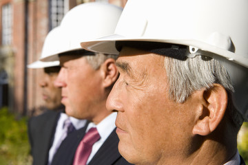 Small group of businessmen in hardhats, side view