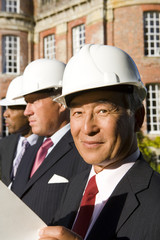 Small group of businessmen in hardhats, one with blueprint, portrait