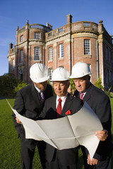 Small group of businessmen in hardhats looking at blueprint by manor house