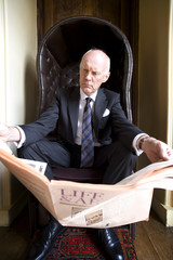 Businessman in armchair with newspaper