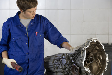 Female mechanic looking at engine part