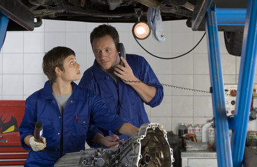 Female mechanic looking at colleague on telephone by engine of elevated car