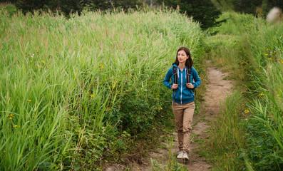 Hiker woman going among high grass in summer