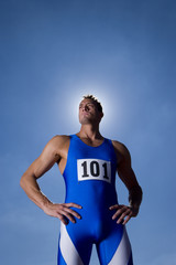 Male athlete with hands on hips, low angle view