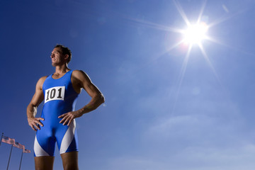Male athlete with hands on hips, low angle view (sun flare)