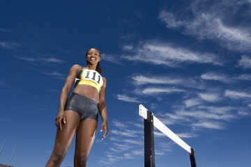 African female athlete standing near hurdle