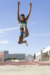 African female athlete mid-air during long jump
