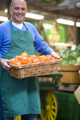 Green grocer with basket of peppers, smiling, portrait