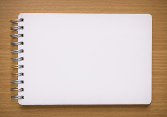 blank white spiral notebook on wood background