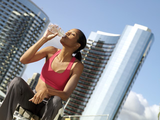 Young woman taking break from exercising outdoors, drinking from bottle of water (tilt)