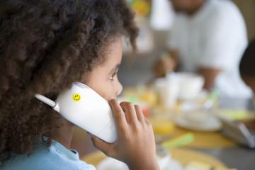 Girl (6-8) on telephone, close-up