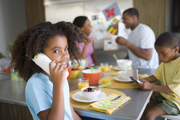 Girl (6-8) on telephone by family at breakfast table, smiling, portrait