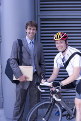 Businessman by bicycle courier, smiling, portrait