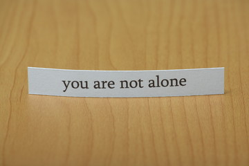 The phrase you are not alone typed on a strip of paper