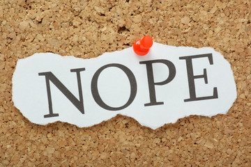 The word Nope on a piece of paper pinned to a cork notice board
