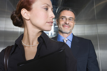 Businessman and woman in elevator, close-up