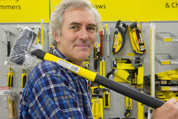 Man with sledge hammer in hardware store, portrait