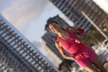 USA, California, San Diego, woman wearing pink sports vest and shorts, jogging, listening to MP3 player strapped to arm, smiling, marina in background (tilt)