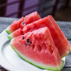 slices of watermelon on a plate on a wooden background