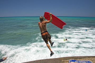 man jumping from pier with body surf