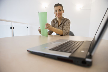 Businesswoman working at desk in office, holding green file, smiling, portrait, laptop in foreground, focus on background, surface level