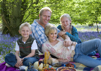 Family picnicking in field of bluebell flowers
