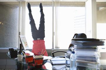 Man standing on head in office