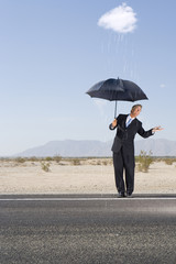 Businessman holding umbrella in desert