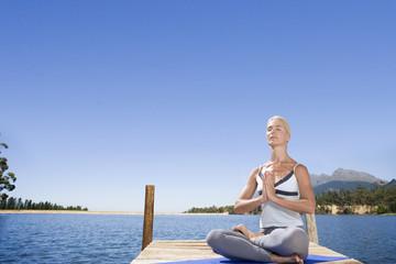 Woman meditating on lake dock