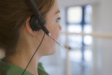 Woman wearing telephone headset on ear, side view, close-up (differential focus)