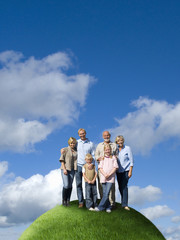Multi-generational family on top of grassy globe