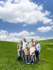 Multi-generational family standing in field
