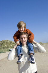 Portrait of father carrying son on shoulder
