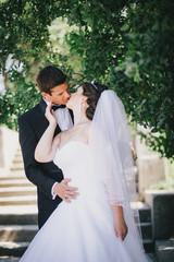 Happy bride and groom posing in a park