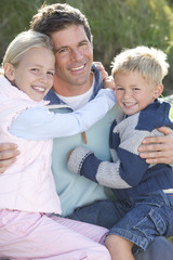 Portait of mid adult man with son and daughter