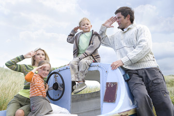 Young family sitting on boat at beach saluting