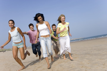 Young adults running on beach