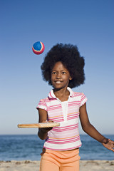 Girl (8-10) playing with bat and ball on sandy beach, smiling, front view, portrait