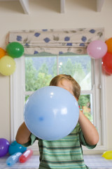 Boy blowing up birthday balloons