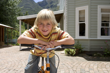 Boy riding bicycle in patio