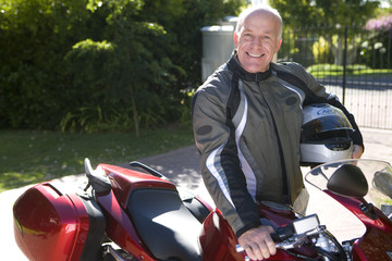 Mature man posing with motorcycle