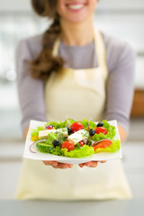 Closeup on young housewife showing greek salad
