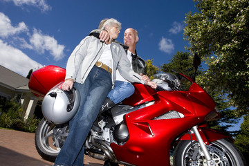 Mature couple posing with motorcycle