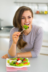 Happy young housewife eating greek salad