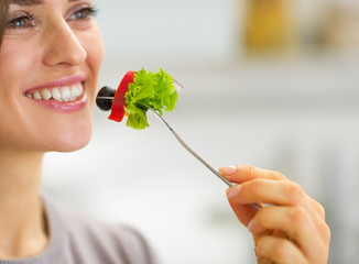 Closeup on happy young housewife eating vegetables